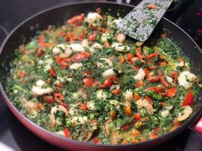 ingredienserna av scampi pastan puttrar ihop tillsammans i stekpannan