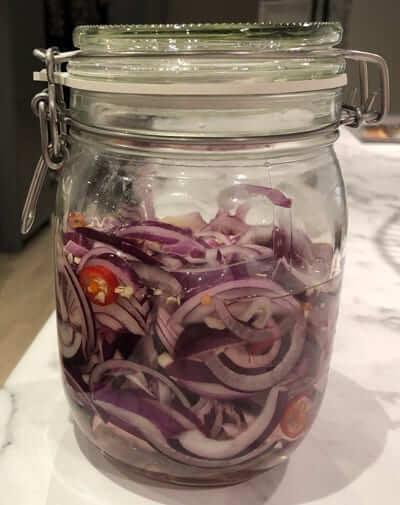 rödlök med chili och ättika i en glasburk