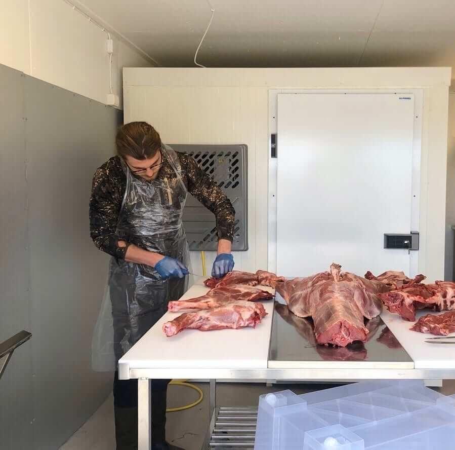 Adrian står och styckar till köttbitar i slakteriet, av sitt tidigare fällda vildsvin