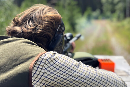 kille skjuter med ett vapen mot en måltavla