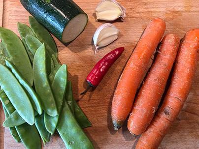 chili, zucchini, sockerärtor, morötter och vitlök som ligger på en skärbräda gjort av trä