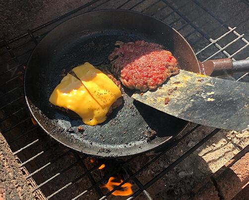 Hamburgerkött med ost på en stekpanna på grillen